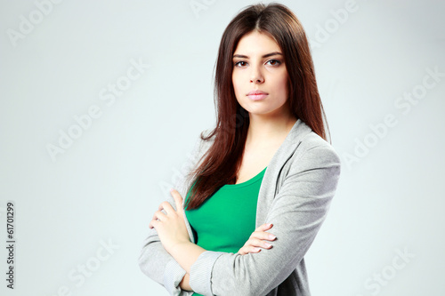 Beautiful woman standing with arms folded on gray background