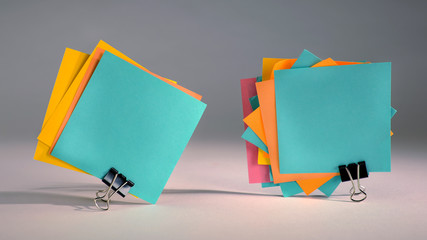 Paper notes fastened with paper clips on gray background.