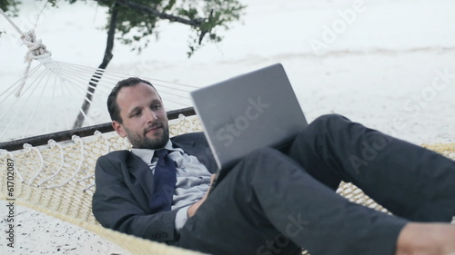 Businessman working on laptop, lying on hammock on the beach