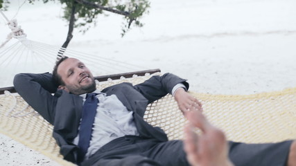Happy businessman relaxing on hammock on exotic beach
