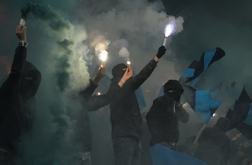 Soccer fans in smoke with fireworks
