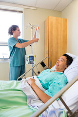 Nurse Adjusting IV Drip On Rod With Patient On Foreground