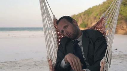 Sad, bored businessman sitting on hammock on exotic beach