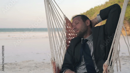 Young businessman sleeping on hammock on exotic beach