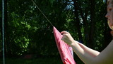 houseworker woman hang washed laundry on clothes-line and clip
