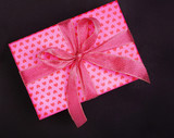 pink gift box in heart pattern on black background