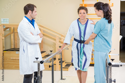 Physical Therapist With Doctor Assisting Female Patient In Walki