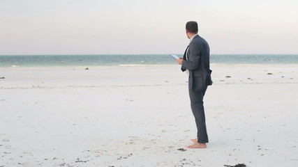 Lost businessman with tablet computer on exotic beach