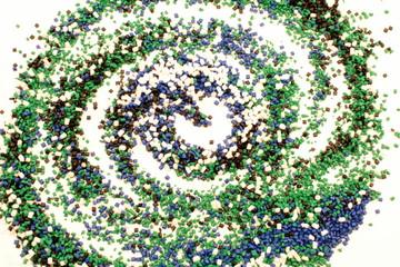 Un disegno di spirale fatto con tanti piccoli sassi di plastica