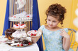 Elegant little girl posing with plate of sweets