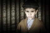 Frowning child in vintage clothes and hat