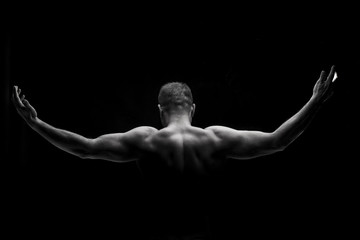 Rear view of a muscular man with arms stretched out on black bac