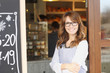 Woman standing in front of coffee shop - 61704886