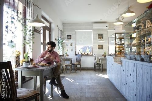 Młody mężczyzna siedzi w kawiarni.