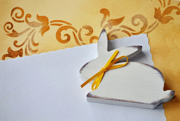 Hase aus Holz auf Papier mit floralem Hintergrund
