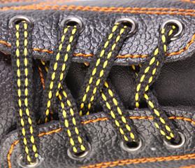 Shoe laces close up with orange stitches.