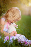 Fototapety Cute little girl with a bunny rabbit has a easter at green grass
