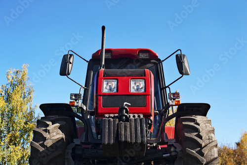 Modern red tractor on a blue sky background