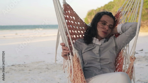 Young businesswoman sleeping on hammock on exotic beach