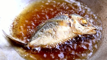 frying mackerel fish in pan with vegetable oil
