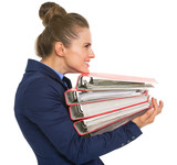 Profile portrait of happy business woman with stack of folders