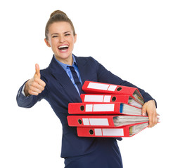 Smiling business woman with stack of documents showing thumbs up