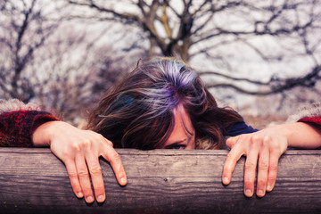 Woman peeping from behind wooden beam