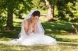 Beautiful worried bride sitting at park