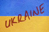Ukraine flag painted on old concrete wall with UKRAINE inscripti