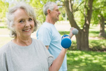 Mature couple using dumbbells at park