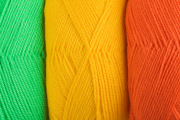 background of yarn skeins in yellow, orange and green colors