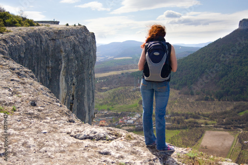 A girl standing on the edge of the high mountain and looking ahe