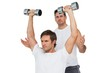 Male trainer assisting man with dumbbells