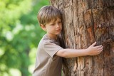 Boy hugging a tree at park