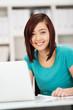 motivierte junge frau arbeitet am laptop