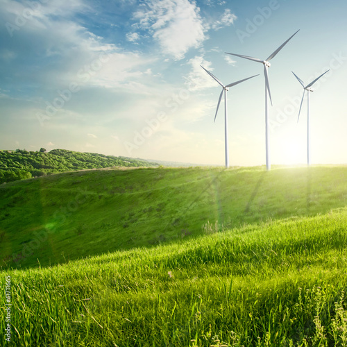Foto op Canvas Weide, Moeras Wind generators turbines on sunset summer landscape