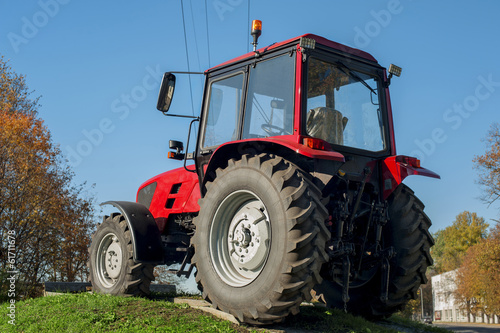 canvas print picture Modern red tractor on a blue sky background