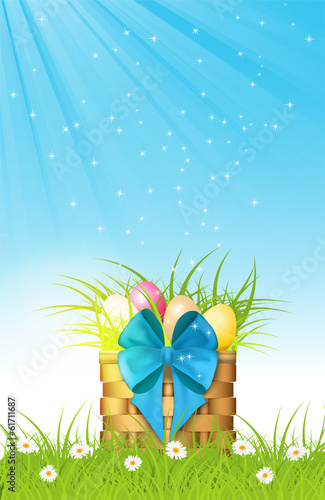 wooden basket with easter eggs on fresh grass