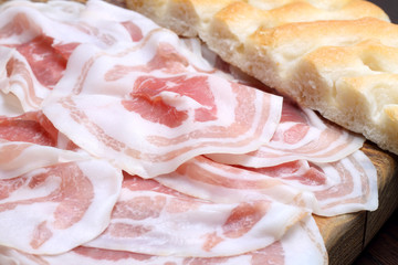 Bacon slices with focaccia on wooden cutting board