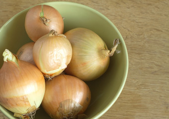 Ripe onions lies in green bowl on wooden surface close-up