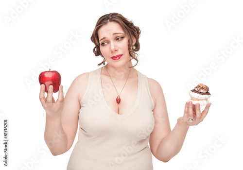 Plus size woman making choice between apple and pastry
