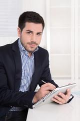 Attraktiver Geschäftsmann im Büro mit Tablet PC