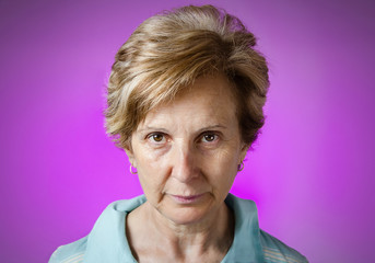 Real serious woman portrait over purple background