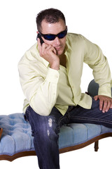 Man in trendy outfit with sunglasses talking on cell phone