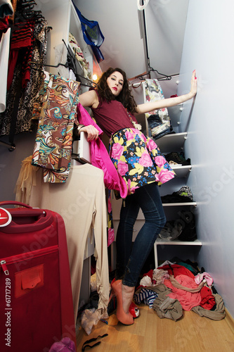 Beautiful girl in a woman's wardrobe