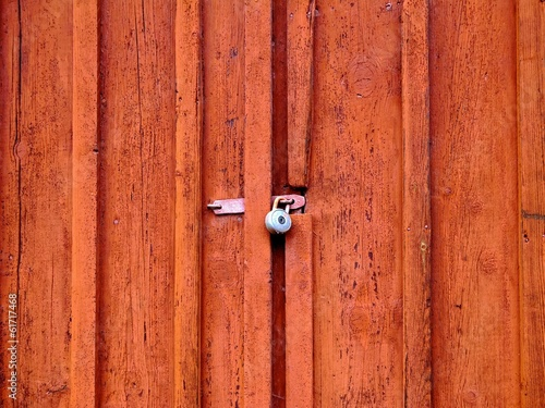 Old red door with a padlock.