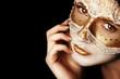 Задумчивая девушка в маске на черном фоне