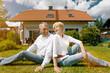 Senioren Paar sitzt vor Haus in Garten