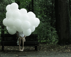 Sentimentality. Woman with Balloons in the Park on Bench