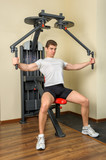 young man does workout at chest fly machine in gym